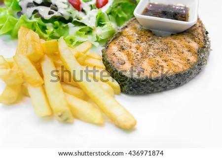 Grilled salmon steak, Serve with french fries and salad vegetables in white plate. - stock photo