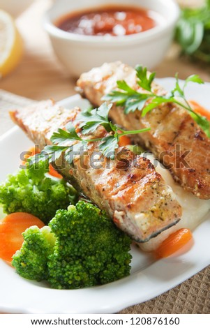 Grilled salmon steak served with broccoli and carrot