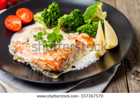 Grilled Salmon Steak with Broccoli, Cream sauce and Lemon Wedges on wooden background, close up - stock photo