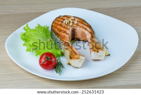 Grilled salmon steak with cedar nut and salad