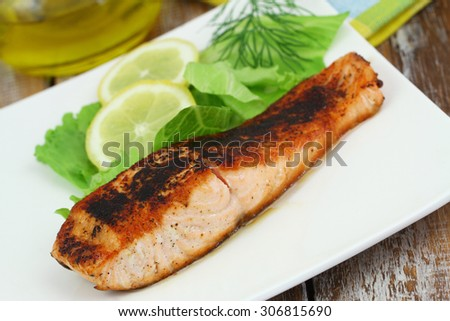 Grilled salmon steak with green salad and lemon on white plate  - stock photo