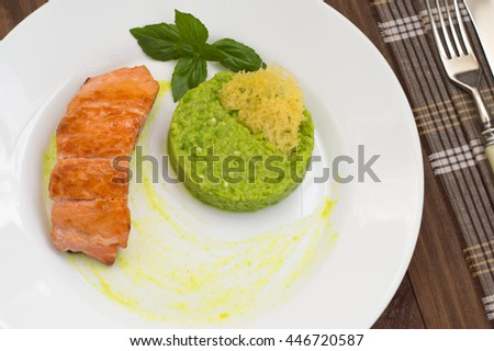 Grilled salmon steak with pea puree, cheese crisps and basil on a plate with the sauce. Wooden rustic background. Top view. Close-up