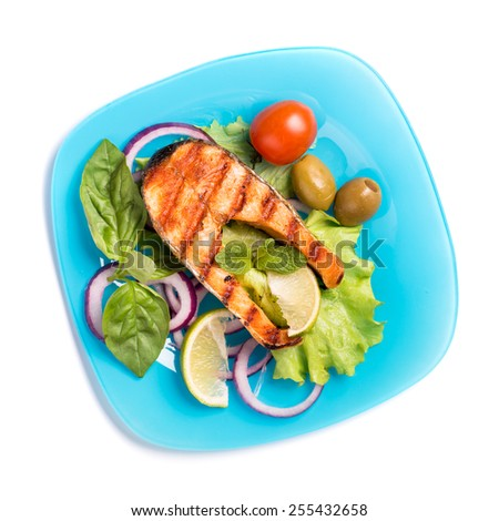 Grilled salmon steak with sliced onion and tomatoes on blue plate isolated on white top view - stock photo