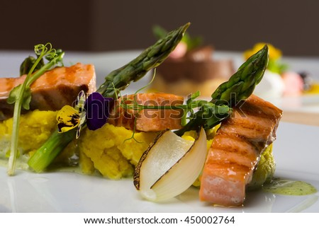 Grilled salmon steaks garnished with puree sauce flower asparagus and vegetables on white background