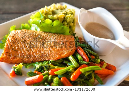 Grilled salmon/trout fillet with potato-spinach mash and vegetables. Indoors closeup. - stock photo
