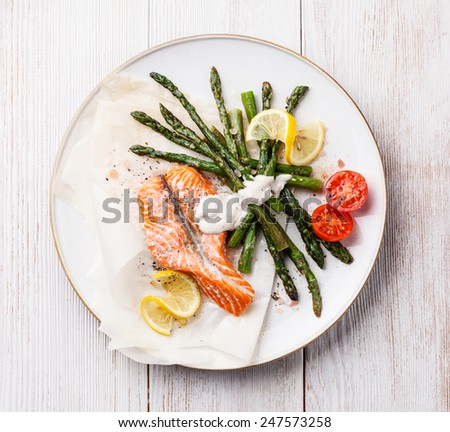 Grilled salmon with asparagus on white wooden background - stock photo