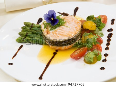 grilled salmon with asparagus,red and yellow tomatoes on white plate - stock photo