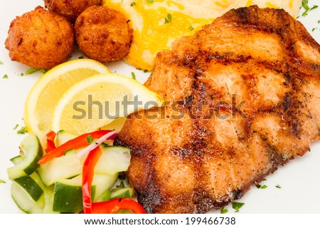 Grilled salmon with cheese mashed potatoes, vegetables, and hush puppies. - stock photo