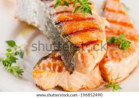 Grilled salmon with fresh herbs. Selective focus - stock photo