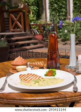 Grilled Salmon with fresh herbs, served on the summer terrace. Selective focus - stock photo