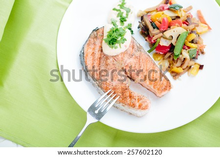 Grilled Salmon with Fresh vegetables on green background - stock photo