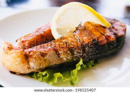 grilled salmon with lemon, asparagus on white plate