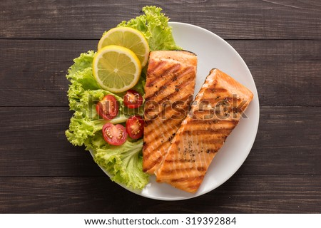 Grilled salmon with lemon,tomato on the wooden background. - stock photo