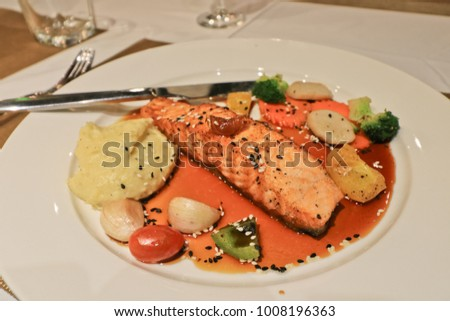 Grilled salmon with mashed potatoes and stewed spinach on white plate