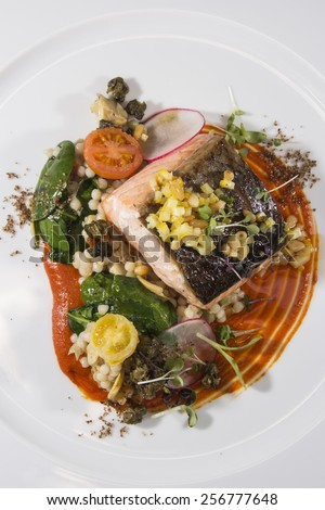 Grilled salmon with pearl cous cous, artichoke ragout, red bell pepper puree and lemon-pine nut Gramoulata  - stock photo