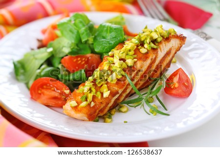 grilled salmon with pistachio and fresh salad on white plate