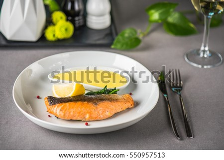 Grilled salmon with sauce in the white plate closeup. Served restaurant table.
