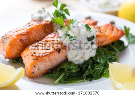 Grilled Salmon with Spinach, Tartare Cream and Lemon Wedges - stock photo