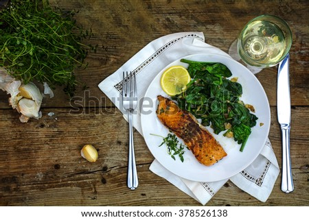 grilled salmon with thyme, lemon and spinach on a white plate  and white wine on a dark rustic wooden table, top view from above on a mediterranean vegetarian low carb dish,  - stock photo