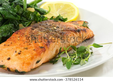 grilled salmon with thyme, lemon and spinach on a white plate, homemade vegetarian low carb dish, close up with selected focus, narrow depth of field - stock photo