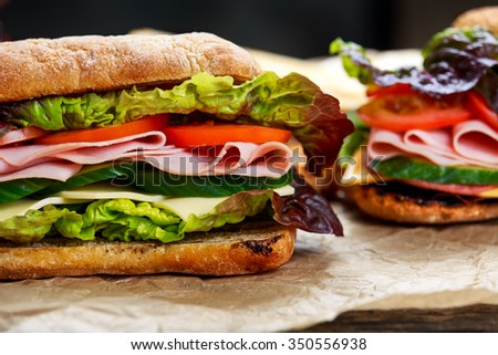 Grilled Sandwich with lettuce, slices of fresh tomatoes, cucumber, red onion, salami, ham and cheese - stock photo