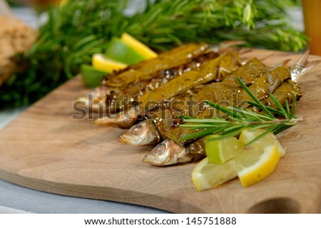 Grilled sardine fish wrapped in vine leaves, served with lemon and rosemary; Greek food - stock photo