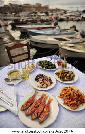 Grilled sardine, octopus, shrimp with olive oil and white wine, traditional Greek food at the restaurant near the bay, island of Crete, Greece - stock photo
