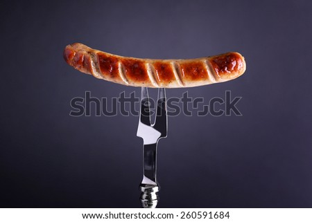Grilled sausage on fork on black background - stock photo