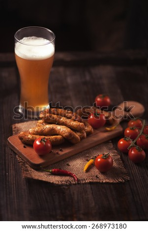 Grilled sausage with beer on wodden table - stock photo