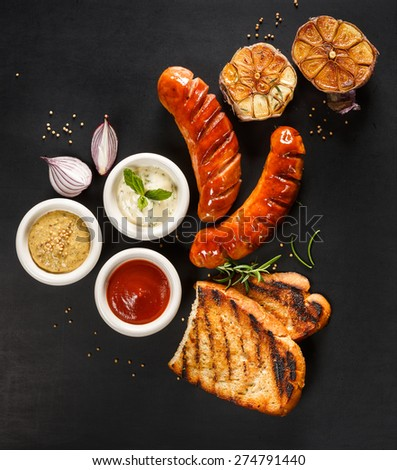 Grilled sausage with different kinds of dips on a black background - stock photo