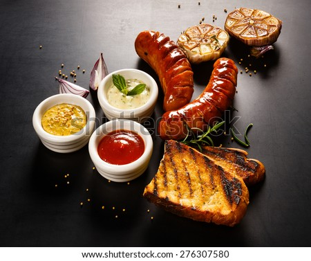 Grilled sausage with different kinds of dips  on a blackboard background - stock photo