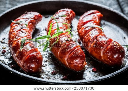 Grilled sausage with fresh rosemary on hot barbecue dish - stock photo