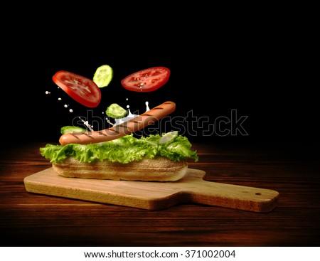 Grilled sausage with fresh vegetables falls on crispy bun, hotdog concept. - stock photo