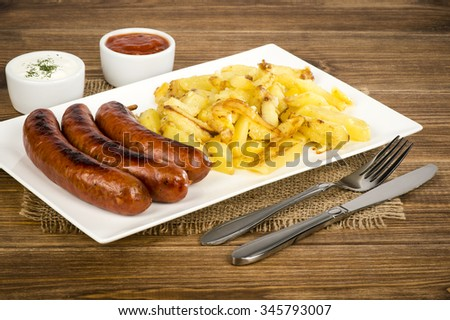 Grilled sausages and fried potatoes on the white plate on the rustic surface.