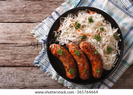 grilled sausages and sauerkraut on a plate on a table close-up. horizontal top view
