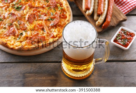 Grilled sausages, delicious pizza and glass of beer on wooden table, close up - stock photo