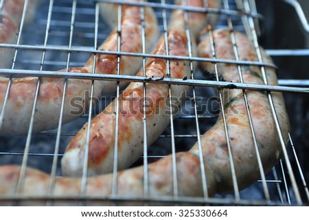 Grilled sausages on the barbecue grill at picnic