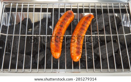 Grilled sausages on the grill grate of the barbecue - stock photo