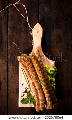 Grilled sausages on wooden board from above  - stock photo