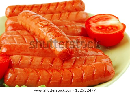 grilled sausages served on green dish with tomato