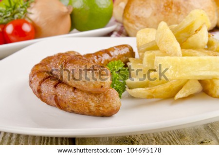 grilled sausages with chips on a plate