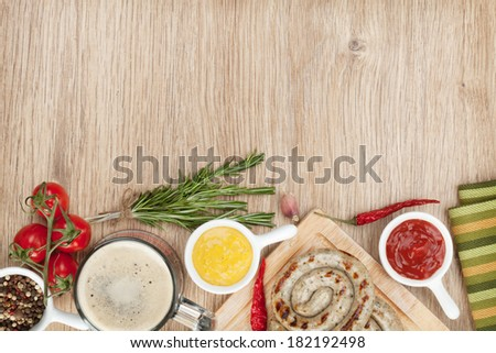 Grilled sausages with ketchup, mustard and mug of beer. Over wooden table background with copy space - stock photo