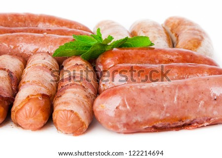 Grilled sausages with mint over white, closeup - stock photo