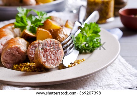 Grilled sausages with potatoes on wooden background. Selective focus. - stock photo