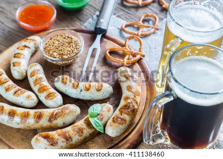 Grilled sausages with pretzels and mugs of beer - stock photo