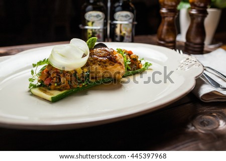 Grilled sea bass fish with vegetables and herbs isolated on wooden background