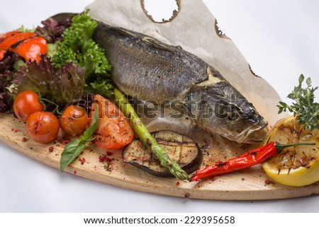Grilled sea bass fish with vegetables isolated on white background - stock photo