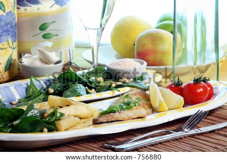 Grilled Sea Bream, chips, cherry tomatoes and baby spinach salad with pine nuts. Wine glass behind. - stock photo