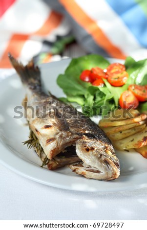 grilled seabass  served with chips  rocket and tomatoes - stock photo