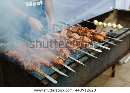 Grilled shish kebab on metal skewer. Chef hands cooking roasted meat barbecue with lots of smoke. BBQ fresh beef chop slices. Traditional eastern dish on charcoal and flame, picnic, street food - stock photo